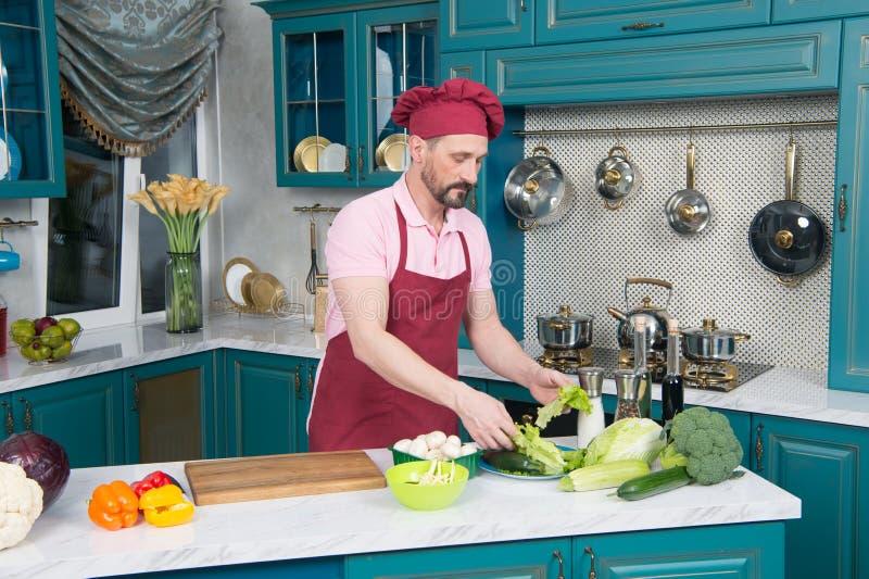 Cozinheiro chefe calmo que toma a alface ao cozinhar sua salada nova imagens de stock royalty free