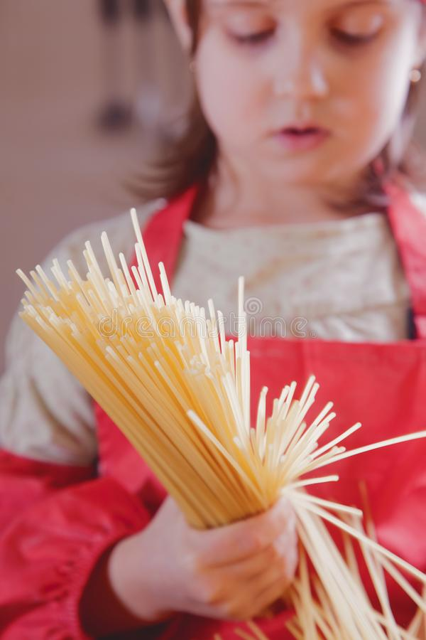Cozinheiro chefe caucasiano bonito atrativo adorável de encantamento da menina da criança que tem o divertimento e que praparing  fotografia de stock
