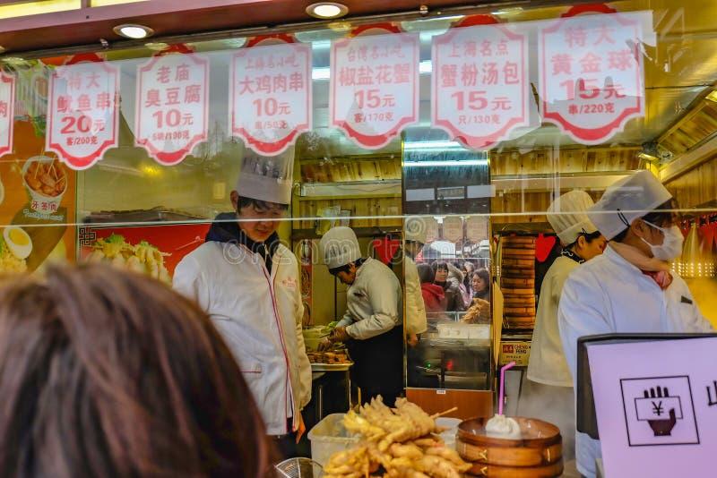Cozinheiro chefe chinês não identificado Cook e alimento tradicional de comércio no jardim de Yuyuan na área velha da cidade em S imagem de stock royalty free