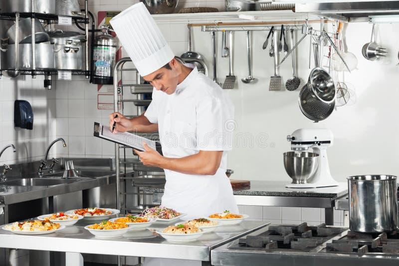 Cozinheiro chefe With Clipboard Going com do cozimento foto de stock royalty free