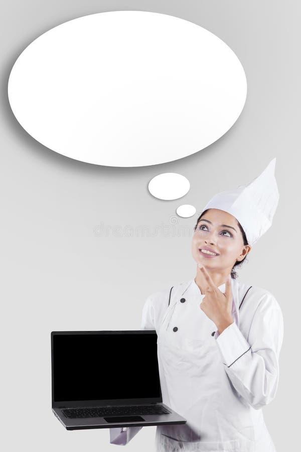 Cozinheiro chefe com bolha do portátil e do discurso foto de stock