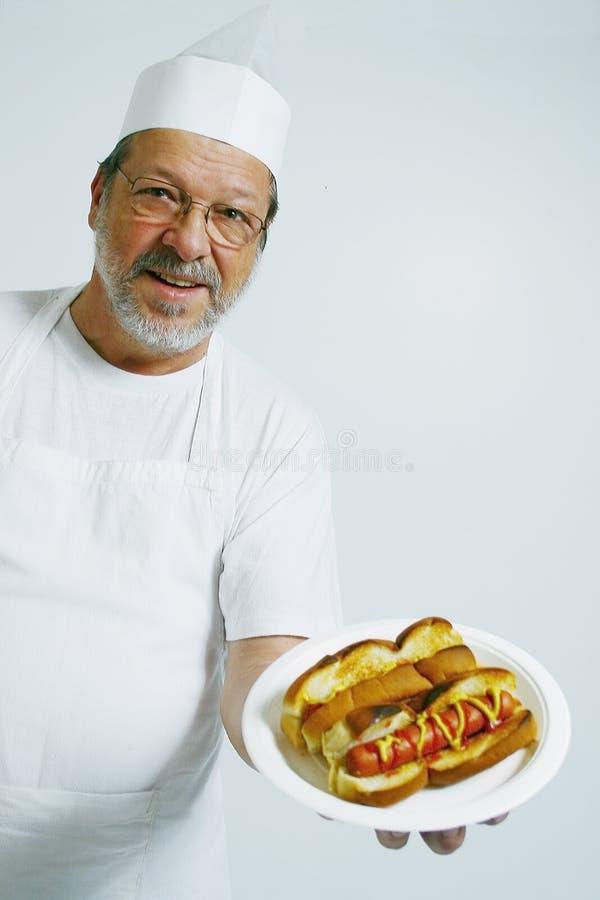 Cozinheiro chefe com cães quentes fotografia de stock
