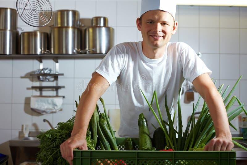 Cozinheiro chefe com legumes frescos fotografia de stock royalty free