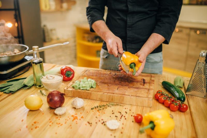 Cozinheiro chefe com pimenta amarela dos cortes da faca na placa de madeira imagem de stock royalty free