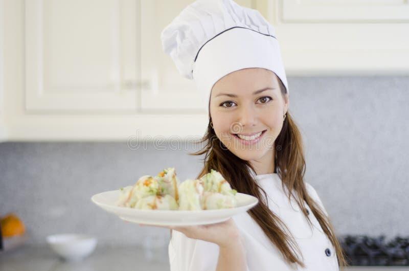 Cozinheiro chefe consideravelmente fêmea com um prato fotos de stock royalty free