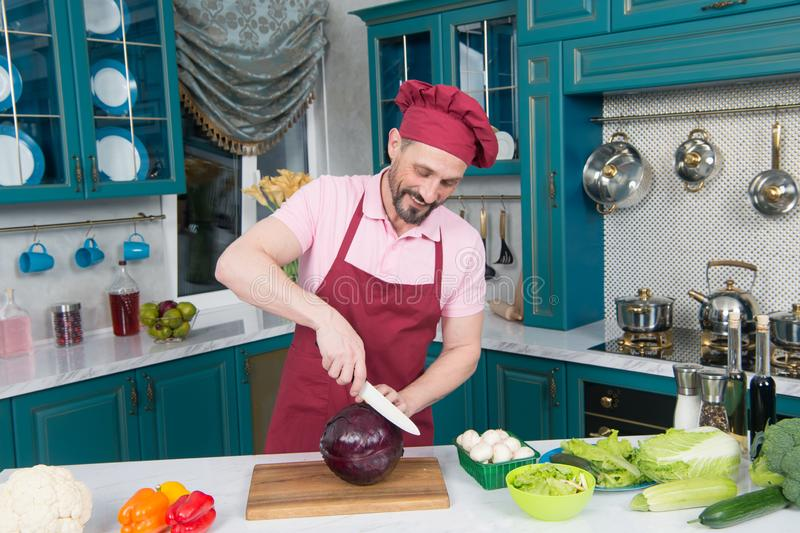 Cozinheiro chefe cuidadoso que sorri ao cortar a couve para uma salada imagem de stock royalty free