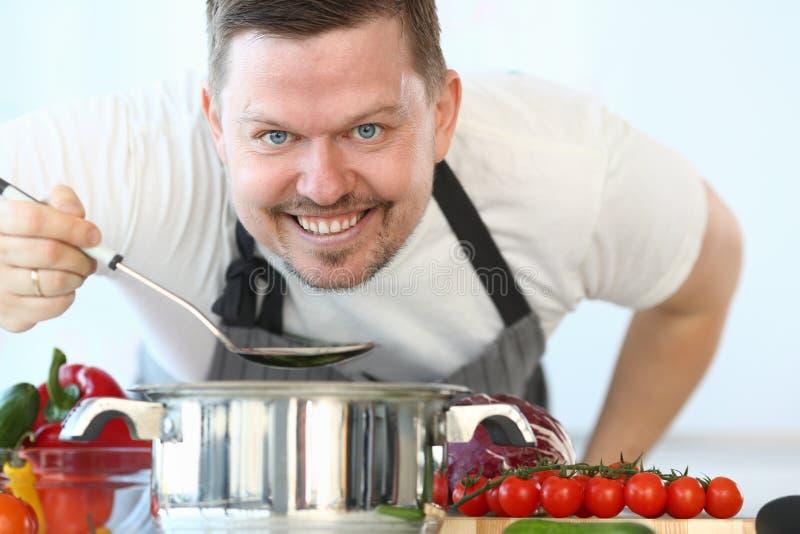 Cozinheiro chefe culinário satisfeito Holding Kitchen Spoon imagem de stock royalty free