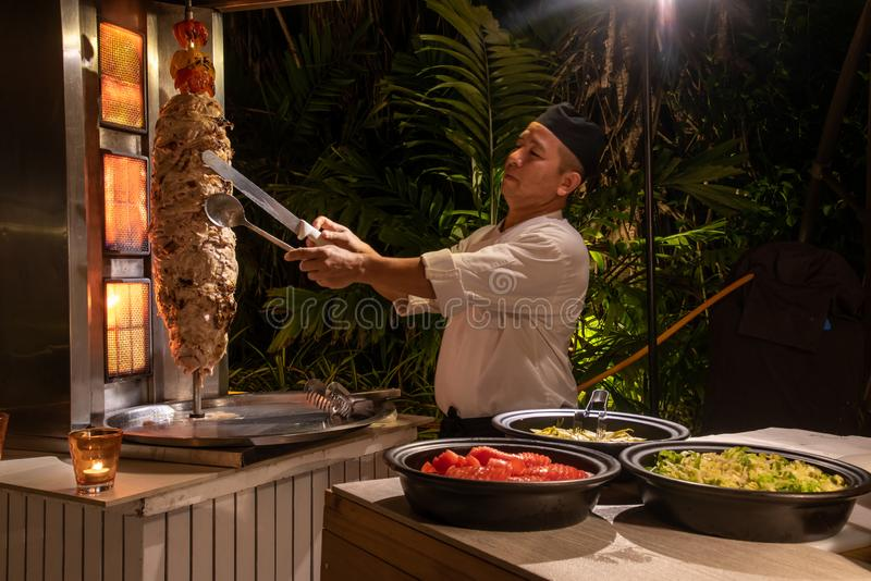 Cozinheiro chefe da cozinha que cozinha o shawarma durante a instalação internacional do jantar da culinária fora no restaurante  imagem de stock