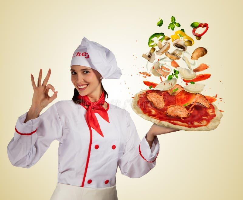 Cozinheiro chefe da jovem mulher com os ingredientes do voo na massa da pizza fotos de stock royalty free