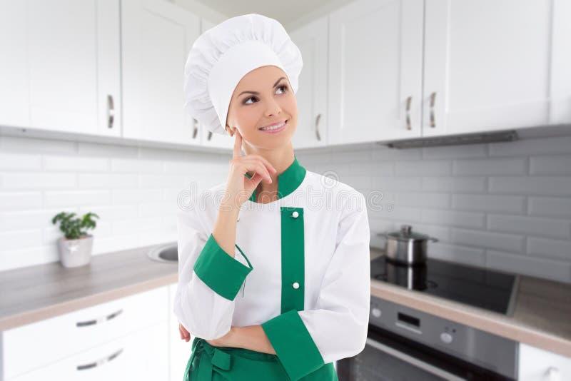 Cozinheiro chefe da jovem mulher que sonha sobre algo no kitche moderno branco fotografia de stock