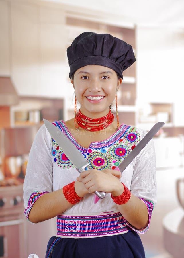 Cozinheiro chefe da jovem mulher que veste a blusa andina tradicional, chapéu de cozimento preto, guardando duas grandes facas, c fotografia de stock