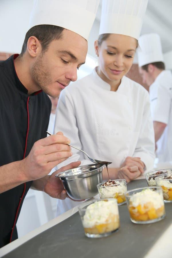 Cozinheiro chefe de pastelaria com os estudantes que fazem o deserto foto de stock