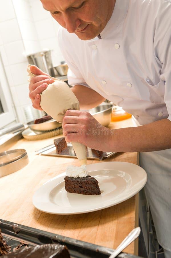 Cozinheiro chefe de pastelaria que decora o bolo com geada foto de stock royalty free