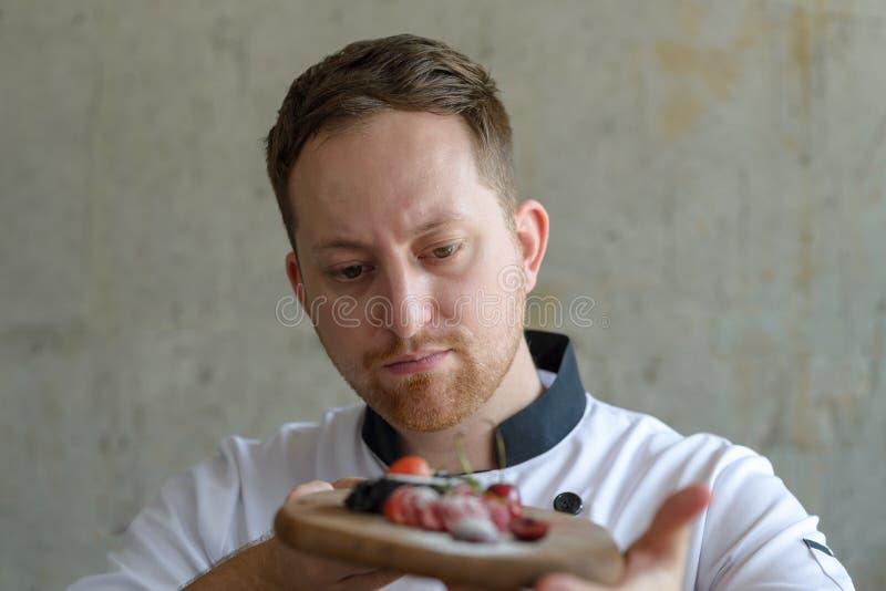 Cozinheiro chefe de pastelaria que olha o bolo em suas mãos foto de stock