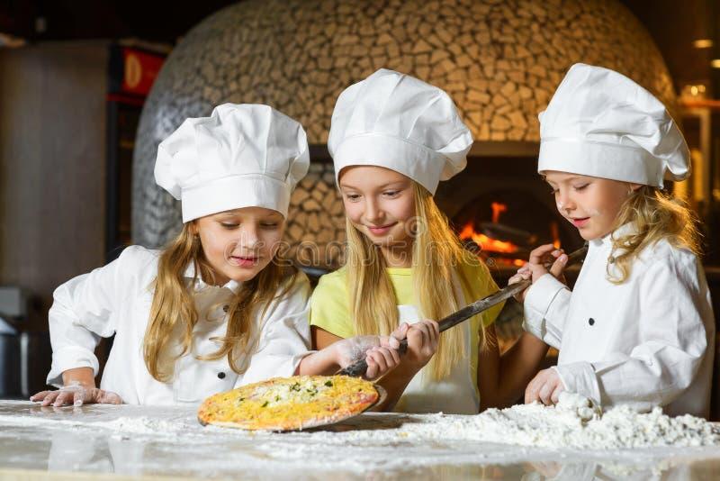 Cozinheiro chefe de sorriso bonito da menina que admira o olhar na pizza foto de stock