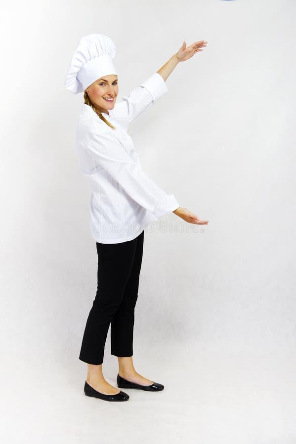 Cozinheiro chefe de sorriso da mulher que dá boas-vindas a lhe a seu local de trabalho imagem de stock