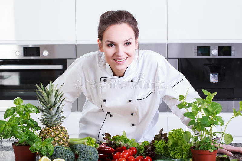 Cozinheiro chefe de sorriso da senhora que prepara um prato fotografia de stock royalty free
