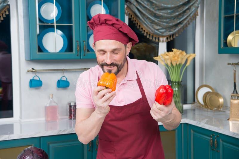Cozinheiro chefe deleitado que sorri ao cheirar a paprika deliciosa fotografia de stock royalty free