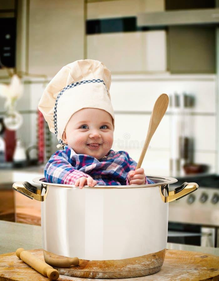 Cozinheiro chefe do bebê em um potenciômetro de aço foto de stock royalty free