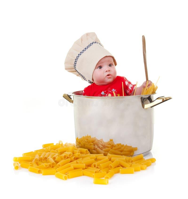 Cozinheiro chefe do bebê em um potenciômetro enorme com massa imagem de stock