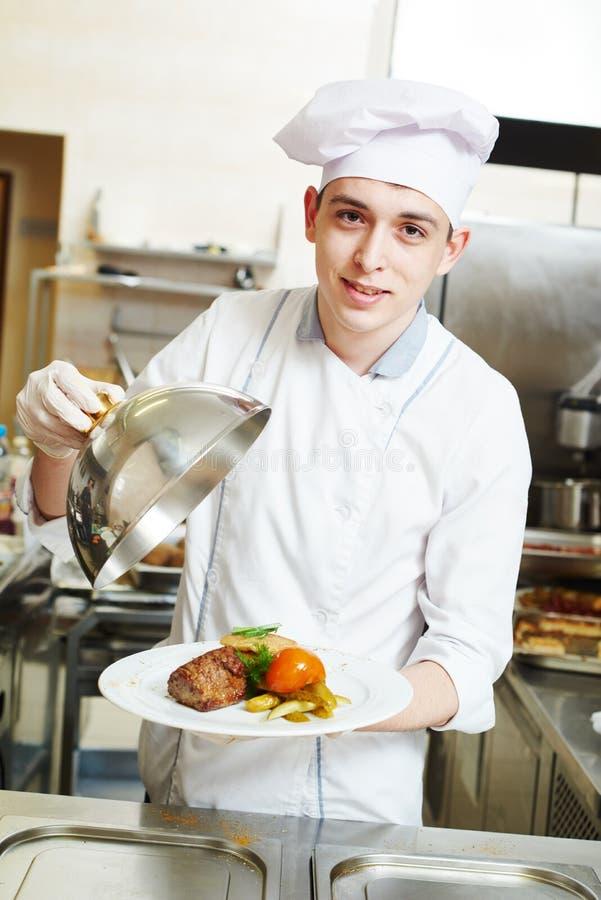Cozinheiro chefe do cozinheiro com alimento na cozinha fotos de stock royalty free