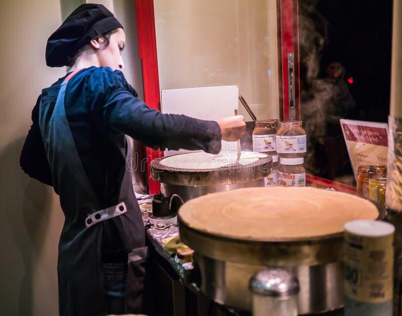 Cozinheiro chefe do crepe da jovem mulher que cozinha sobre chapas para assar do crepe no café de Montmartre fotos de stock