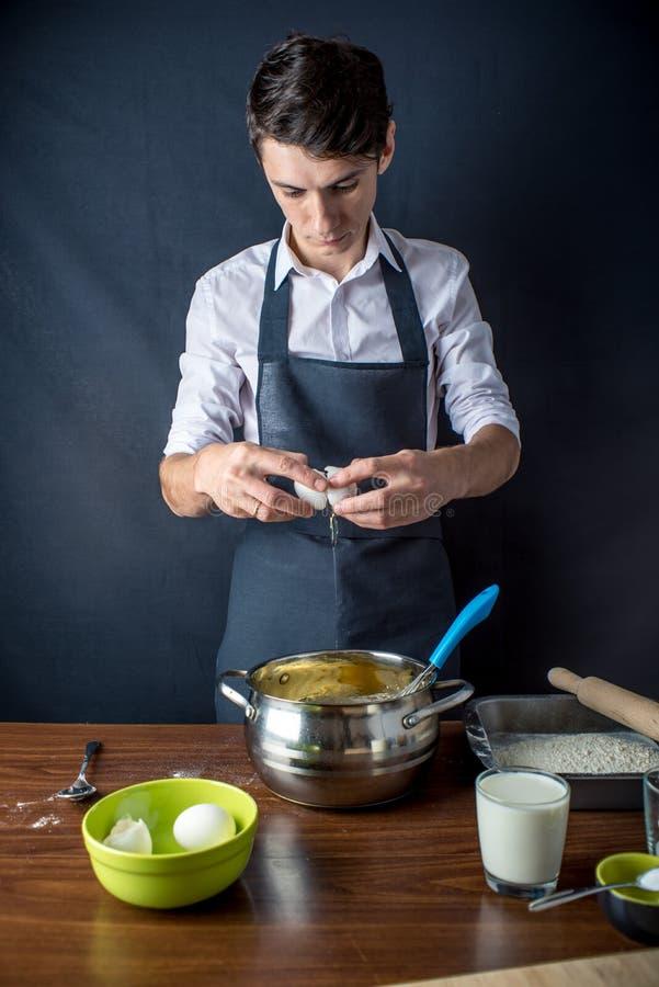 Cozinheiro chefe do homem novo no avental preto que cozinha o bolo com os ingredientes na tabela na cozinha O conceito dos homens fotografia de stock royalty free