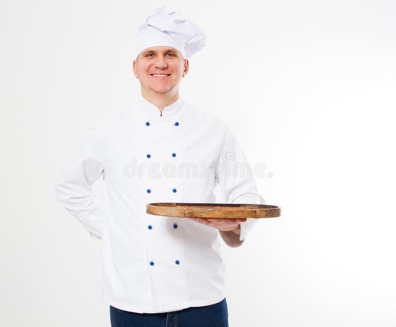 Cozinheiro chefe do sorriso na mesa de corte vazia da posse uniforme isolada no fundo branco fotos de stock royalty free
