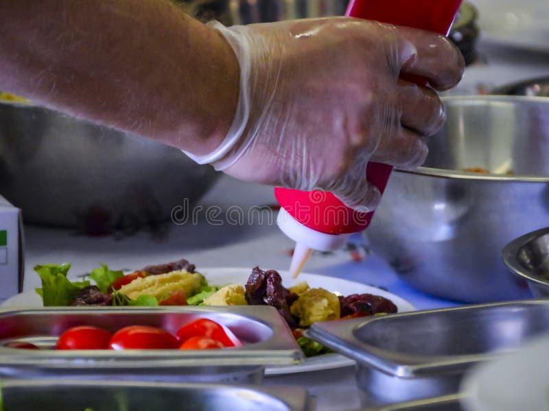 Cozinheiro chefe Drizzling um molho de uma garrafa vermelha em um prato preparado com bacias inoxidáveis ao redor durante o cozim imagens de stock
