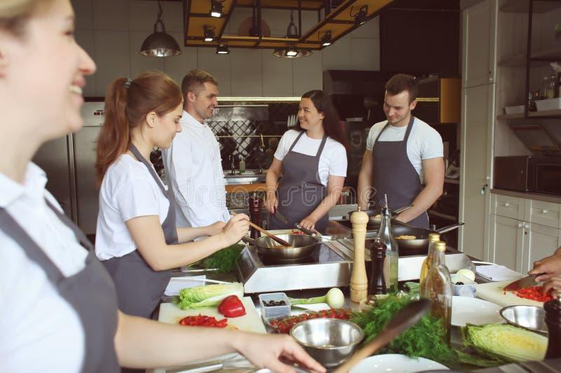 Cozinheiro chefe e grupo de jovens durante aulas de culinária fotos de stock royalty free