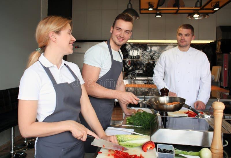 Cozinheiro chefe e grupo de jovens durante aulas de culinária imagem de stock
