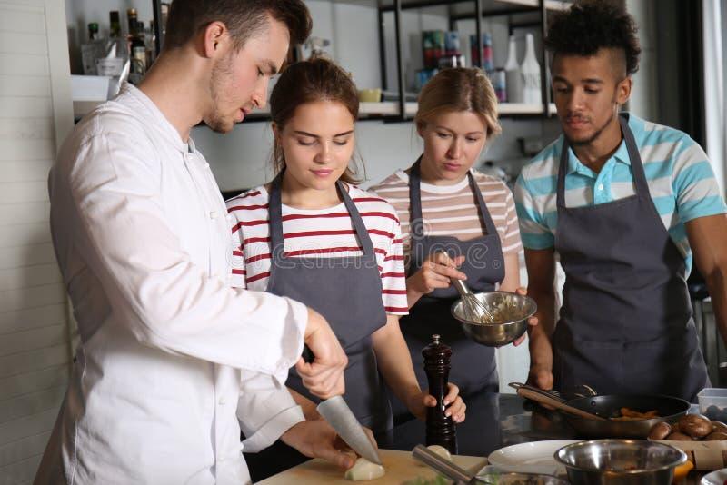 Cozinheiro chefe e grupo de jovens durante aulas de culinária imagem de stock royalty free