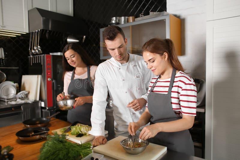 Cozinheiro chefe e grupo de jovens durante aulas de culinária fotos de stock