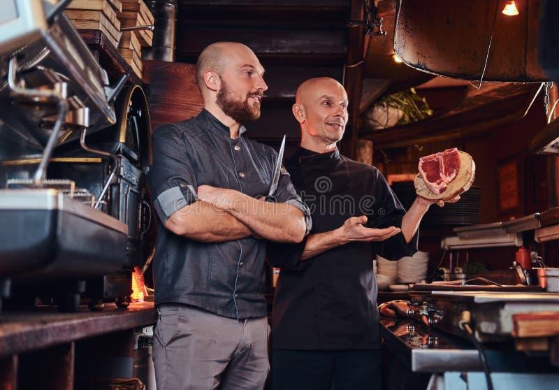 Cozinheiro chefe e seu assistente que apresentam um bife fresco antes de cozinhar fotos de stock