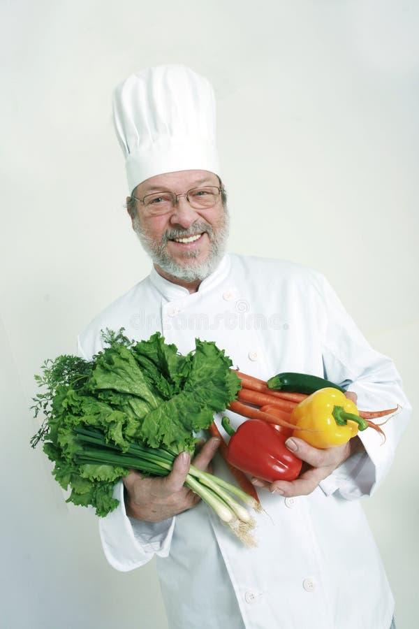 Cozinheiro chefe e vegetais imagem de stock