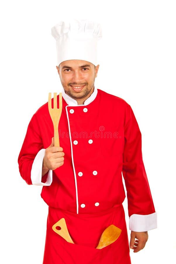 Cozinheiro chefe engraçado que mostra utensílios de madeira fotografia de stock