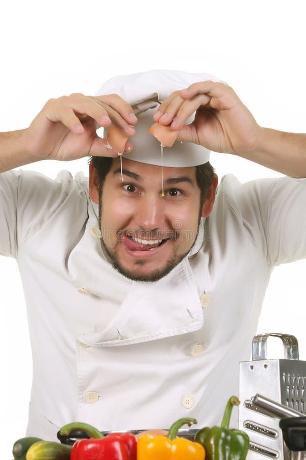 Cozinheiro chefe engraçado que racha um ovo fotos de stock