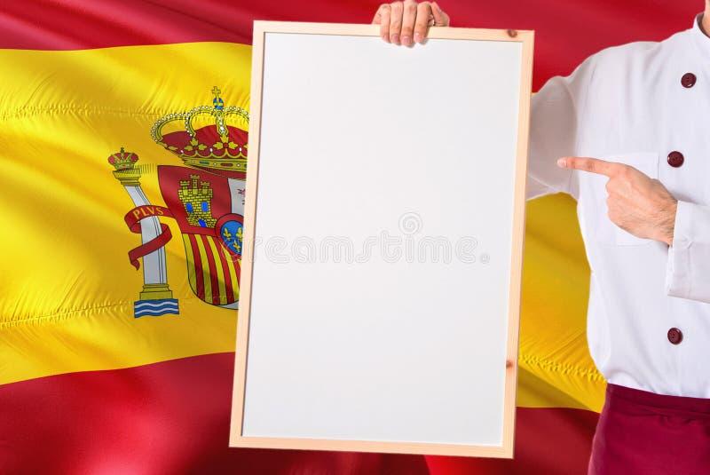 Cozinheiro chefe espanhol que guarda o menu vazio do whiteboard no fundo da bandeira da Espanha Cozinhe o uniforme vestindo que a imagem de stock