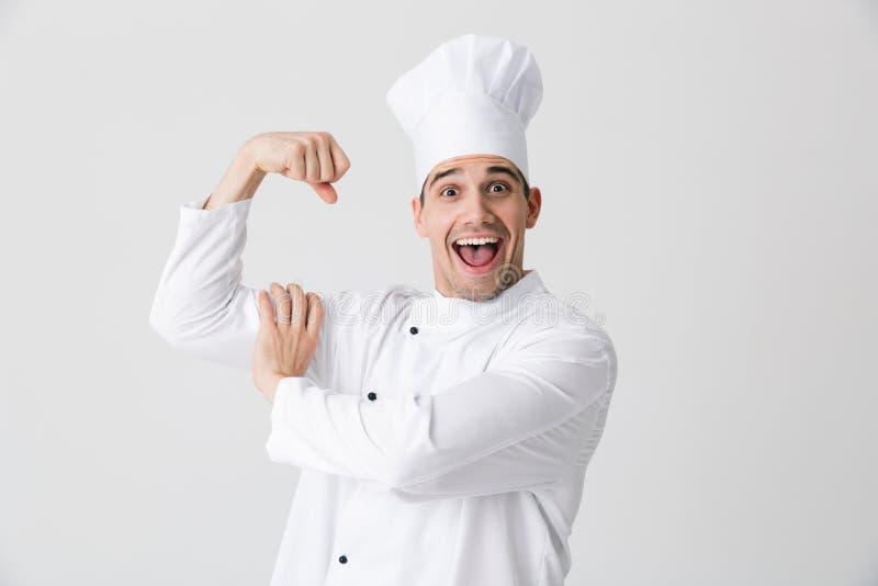 Cozinheiro chefe excitado do homem novo isolado dentro sobre o fundo branco da parede que mostra o bíceps imagens de stock royalty free