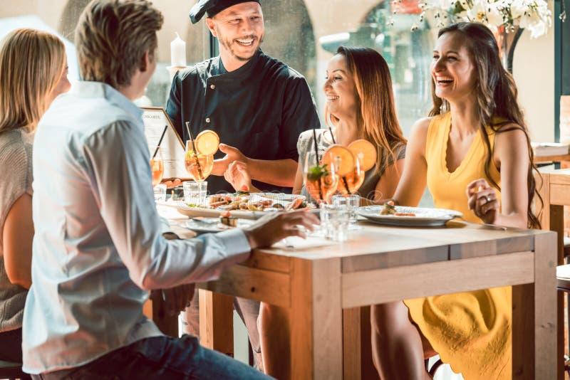 Cozinheiro chefe experiente felicitado por quatro povos em um restaurante na moda fotografia de stock royalty free