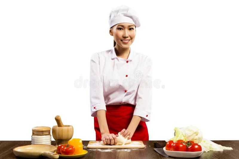 Cozinheiro chefe fêmea asiático que cozinha a massa da pizza foto de stock