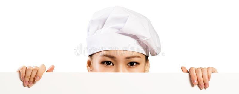 Cozinheiro chefe fêmea asiático que guarda o cartaz para o texto fotografia de stock