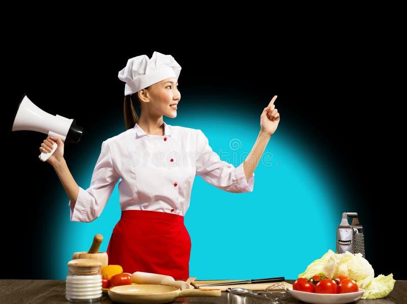 Cozinheiro chefe fêmea asiático que guardara um megafone fotos de stock