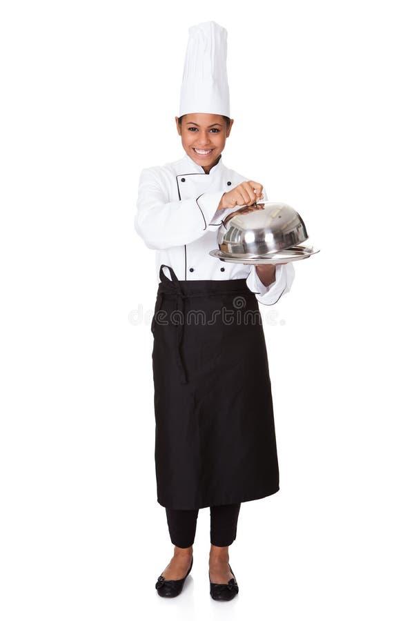 Cozinheiro chefe fêmea com a bandeja de alimento à disposição fotos de stock royalty free