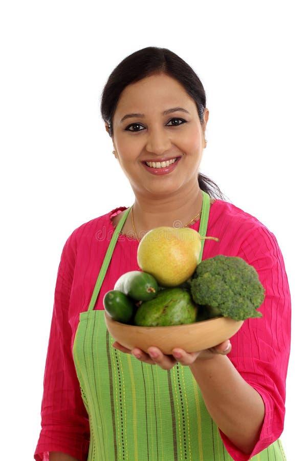 Cozinheiro chefe fêmea de sorriso que mantém a bacia completa dos vegetais e dos frutos fotos de stock royalty free