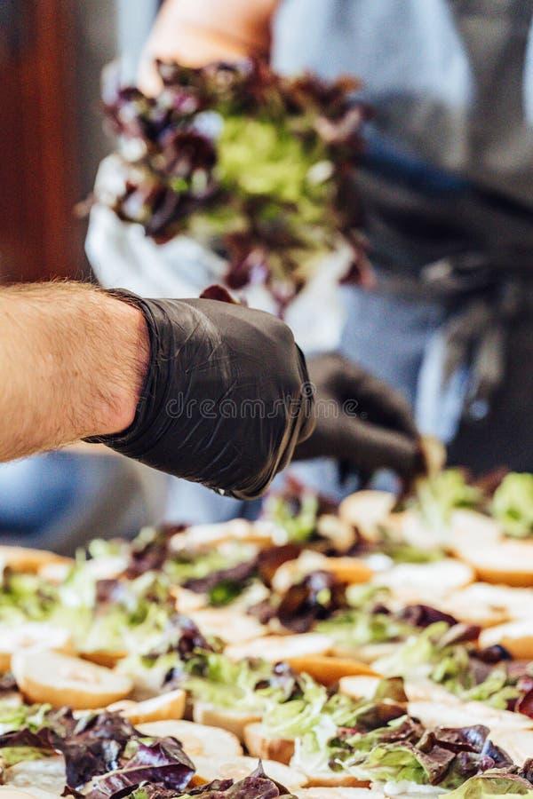 Cozinheiro chefe fêmea e masculino Putting Ingredients dos hamburgueres em uma propagação cortada do pão em uma tabela em luvas p imagem de stock royalty free