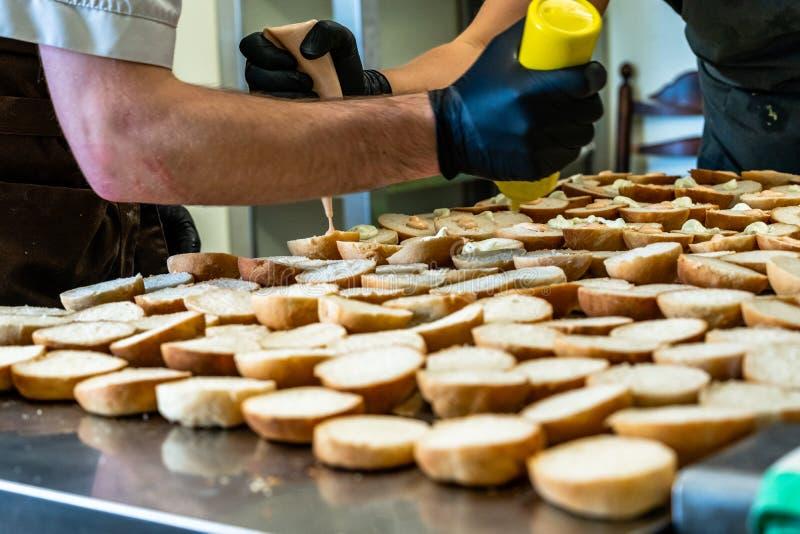 Cozinheiro chefe fêmea e masculino Putting Ingredients dos hamburgueres em uma propagação cortada do pão em uma tabela em luvas p fotografia de stock