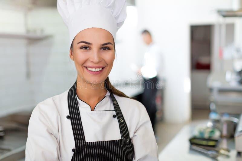 Cozinheiro chefe fêmea na cozinha fotografia de stock