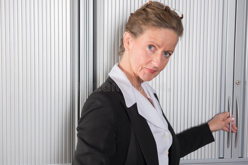 Cozinheiro chefe fêmea no escritório no armário fotos de stock