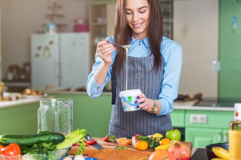 Cozinheiro chefe fêmea novo alegre que cozinha a sobremesa que adiciona o leite condensado no prato em sua cozinha imagens de stock